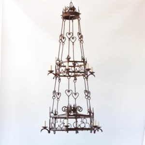 Large French Iron Chandelier with lights on two levels connected by hand forged iron rods with clover and heart motifs in the iron