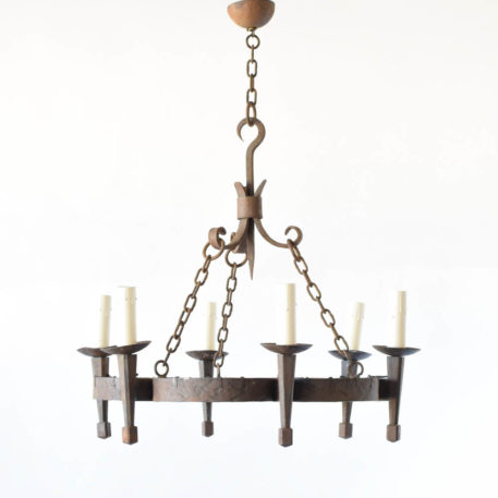 Vintage French chandelier made from thick hand forged flat iron straps with fleur de lis motif behind torch arms