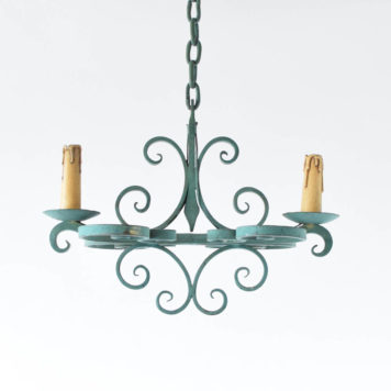 Small French Country Chandelier having an elongated from and nice iron curls