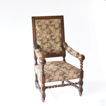 Large wooden arm chair with floral design and balls on arms