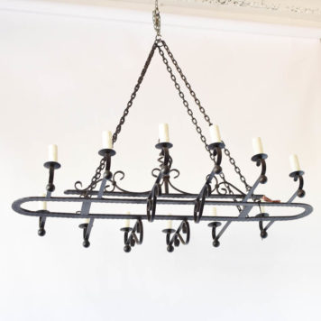 Very large vintage Spanish iron chandelier with central oval frame with hammered design and open basket in the middle