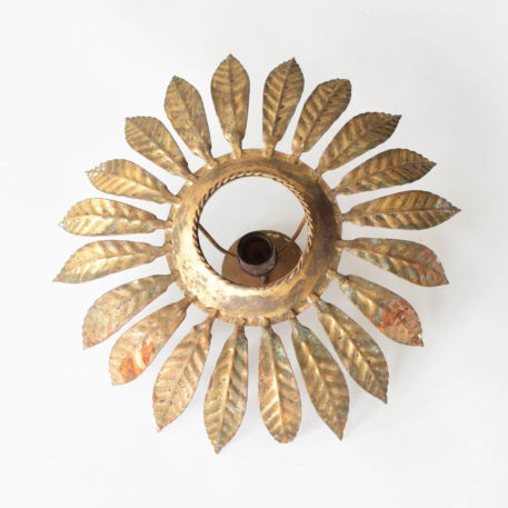 Sun form light from Barcelona made from a simple circle of curved leaves with gilded finish