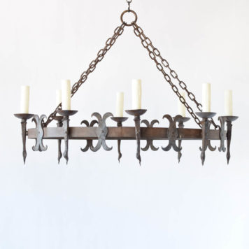 Large Oval shaped chandelier from France with hand forged torch style arms and alternating fleur de lis details